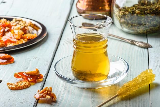 Chá de ervas em copo de armudu com delícias árabes em chapa de metal