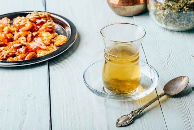 Chá de ervas em copo de armudu com delícias de nozes orientais em placa de metal sobre superfície de madeira clara