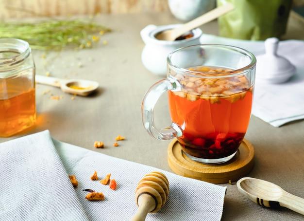 Chá de ervas em copo de vidro na mesa decorada