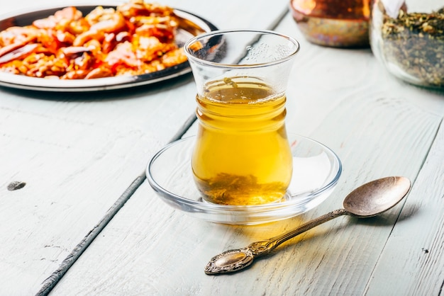 Chá de ervas em copo oriental com delícias de nozes arábicas em placa de metal sobre superfície de madeira clara