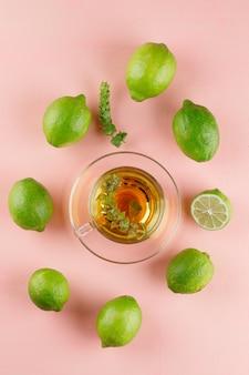 Chá de ervas em um copo de vidro com ervas, limão vista superior em um rosa