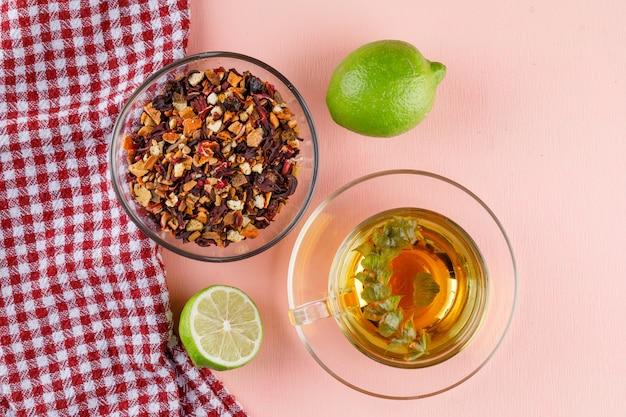 Chá de ervas em um copo de vidro com limão, ervas secas planas leigos na rosa e toalha de cozinha