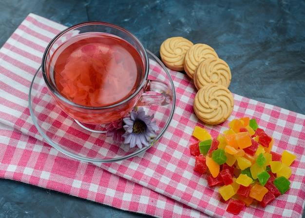 Chá de ervas em uma xícara com doces, flores, biscoitos, vista de alto ângulo em azul e toalha de chá