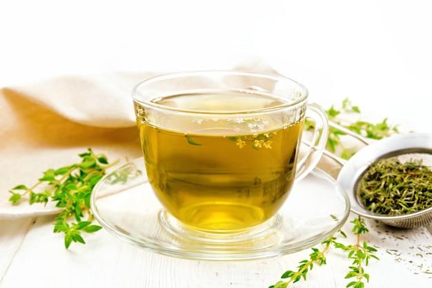 Chá de ervas em uma xícara de vidro de tomilho, uma peneira de metal com folhas secas, um guardanapo de linho contra uma placa de madeira branca