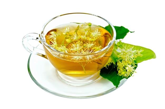 Chá de ervas em uma xícara de vidro, flores de tília frescas isoladas em um fundo branco