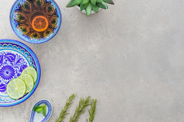 Chá de ervas feito com alecrim; fatias de limão; folhas de hortelã no pano de fundo texturizado cinza