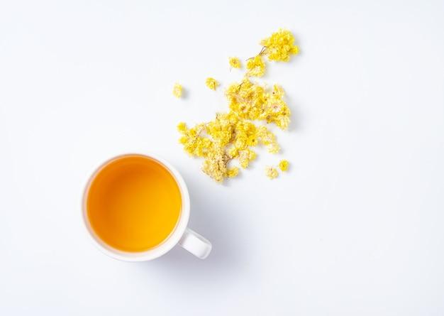 Chá de ervas frescas com flores amarelas em um fundo branco