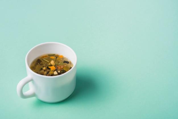 Chá de ervas frescas em fundo verde