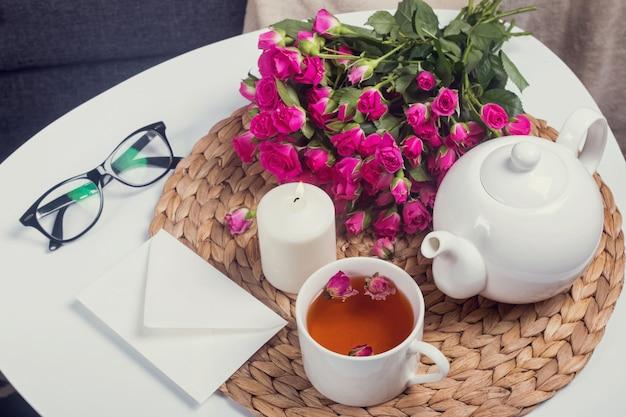 Chá de ervas, rosas cor de rosa, vela acesa na mesa de café branca.