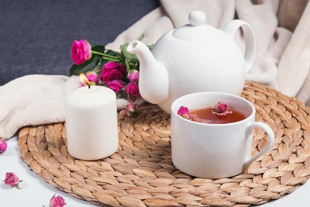 Chá de ervas, rosas e bule de chá na mesa de café