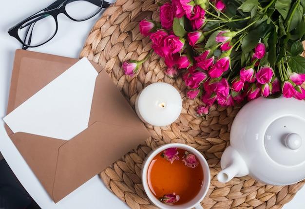 Chá de ervas, rosas, velas e outros objetos na mesa pequena, vista superior