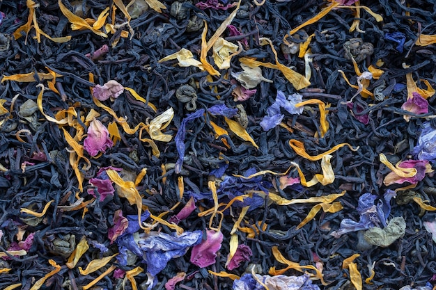 Chá de ervas secas com frutas e pétalas de flores como pano de fundo, vista superior. conceito de alimentação saudável