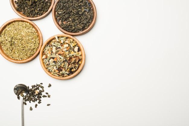 Chá de ervas secas de bem-estar em pratos redondos de madeira contra o fundo branco