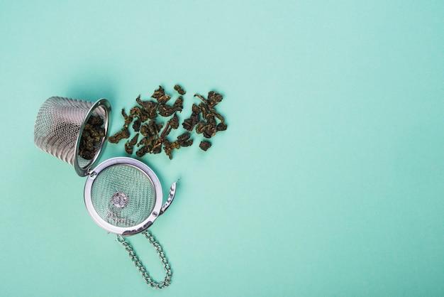 Chá de ervas secas derramado do coador de chá no pano de fundo azul