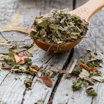 Chá de ervas secas em colher de madeira