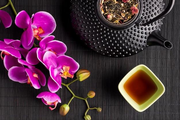 Chá de ervas seco com flor de orquídea rosa e bule no tapete de lugar preto