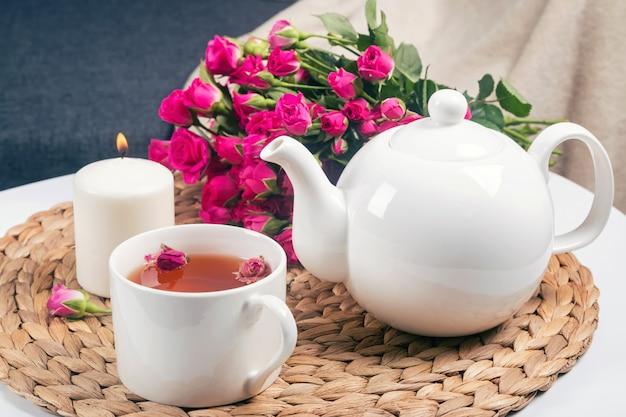 Chá de ervas, velas, bule de chá e lindas rosas em cima da mesa