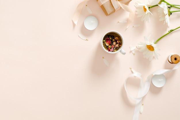 Chá de ervas, velas, fita, caixa de presente, flor de camomila em fundo rosa pastel.