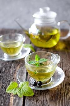 Chá de ervas verde com uma bagas em copo de vidro na mesa de madeira