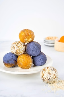 Chá de ervilha borboleta matcha azul caseiro em pó bolas de energia em um prato de cerâmica doces saudáveis feitos de