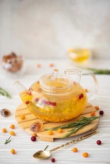 Chá de espinheiro-mar com lingonberry e alecrim em um bule de vidro