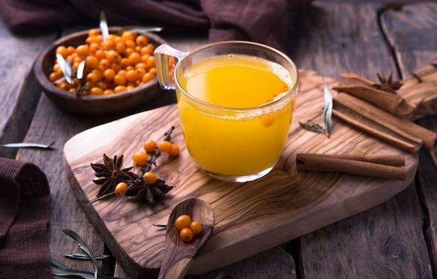 Chá de espinheiro mar em um copo de vidro antes da janela. bebida vitamínica à base de plantas