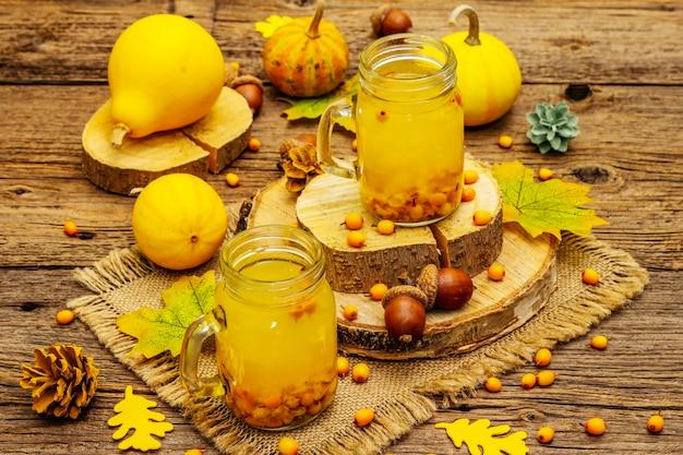 Chá de espinheiro-mar vitaminado e saudável em pequenos potes de vidro com frutas frescas