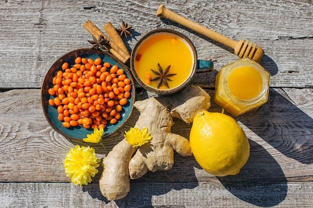 Chá de espinheiro marítimo, mel, limão e gengibre em uma mesa de madeira, o chá anticold é um antioxidante para a saúde