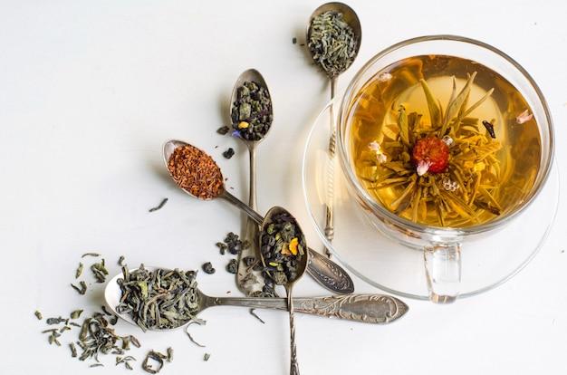 Chá de floração em um copo de vidro e colheres de prata com vários tipos de chá