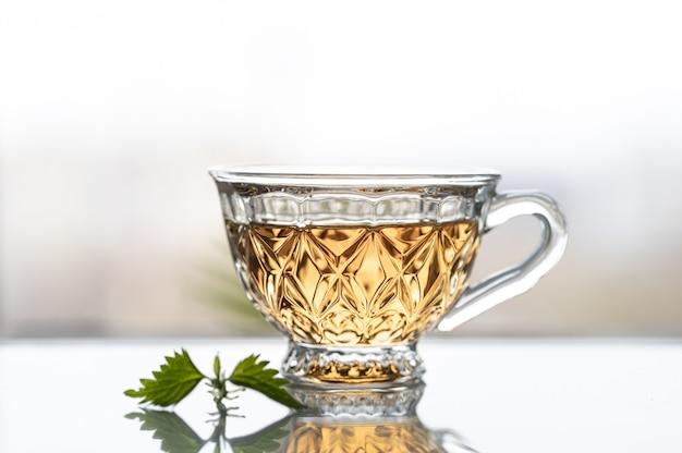 Chá de folhas jovens de urtiga em um fundo de uma janela. copie o espaço