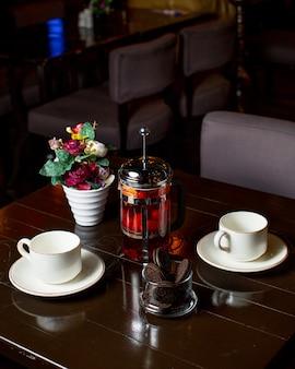 Chá de frutas com biscoitos e copos em cima da mesa