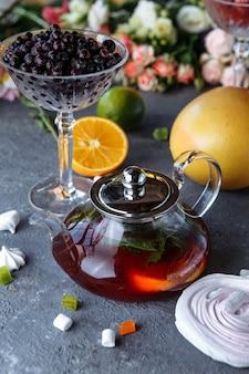 Chá de frutas com hortelã, laranjas e cranberries em um fundo decorativo.