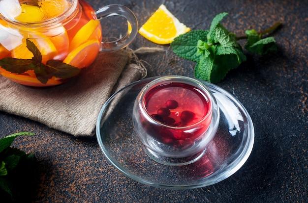 Chá de frutas com sabor caseiro em copo de vidro e bule com laranja acabada de fazer e fatia de limão, frutas, hortelã e mel em fundo escuro e rústico. bebida quente de outono ou inverno. cerimônia do chá
