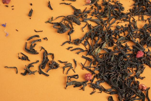Chá de frutas e frutas vermelhas espalhado na textura de chá de fundo marrom