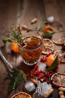 Chá de frutas perfumadas com tangerinas, limões secos e alecrim em uma mesa de madeira. estilo sertanejo.