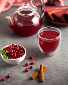 Chá de frutas vermelhas com cranberries, canela, gengibre e hortelã em um bule com uma caneca e tigela de cranberries