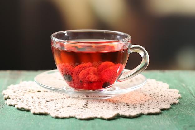 Chá de frutas vermelhas com frutas silvestres em copo de vidro, na mesa de madeira, no fundo brilhante