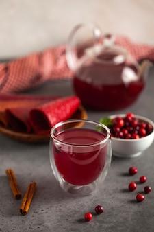 Chá de frutas vermelhas de seus cranberries, chá preto, canela, gengibre e hortelã em um bule com uma caneca e tigela de cranberries