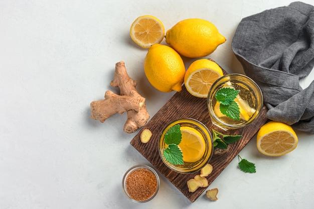 Chá de gengibre com limão e hortelã em um fundo cinza. um chá útil para fortalecer o sistema imunológico.