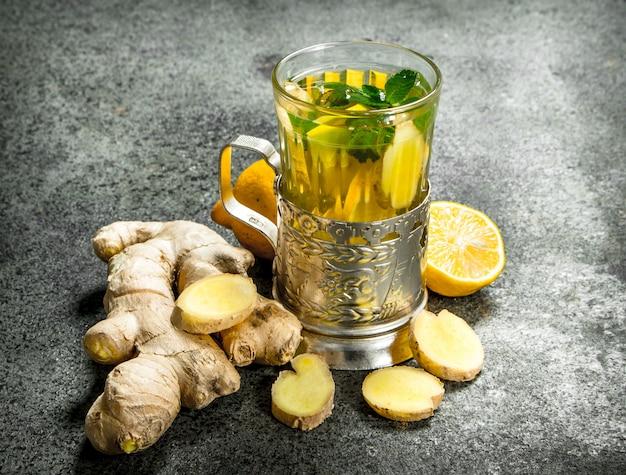 Chá de gengibre com menta e mel. sobre fundo rústico.