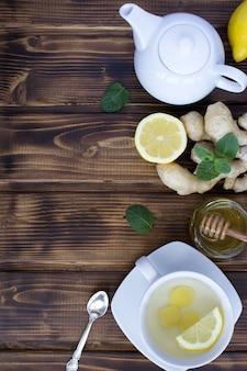 Chá de gengibre e ingredientes no fundo de madeira marrom. vista superior. copie o espaço.