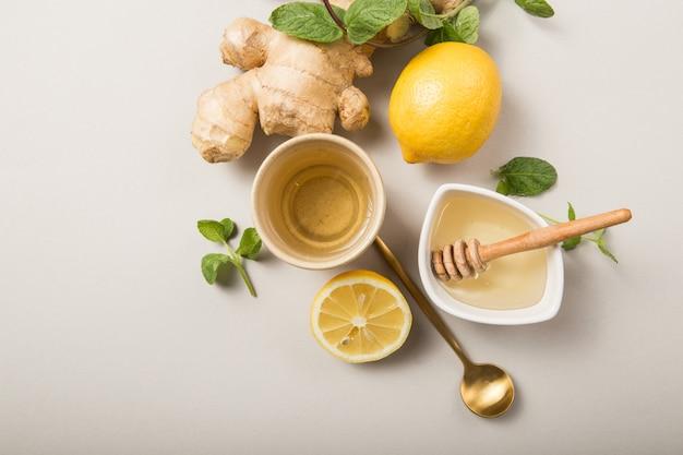 Chá de gengibre e limão com mel. aquecimento do sistema imunológico com cítricos e gengibre. raiz de xícara, mel, gengibre no fundo cinza pastel