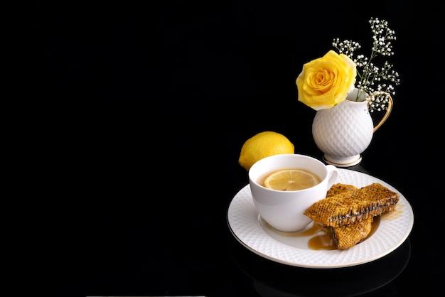 Chá de gengibre mel de limão com favo de mel selvagem em fundo preto.