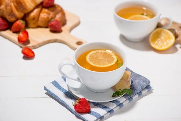 Chá de gengibre saudável com café da manhã em uma mesa de madeira