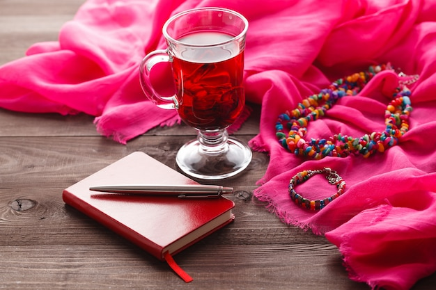 Chá de hibisco e xale de seda rosa na mesa