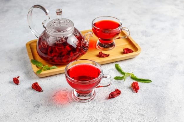 Chá de hibisco quente em uma caneca de vidro e bule de vidro.