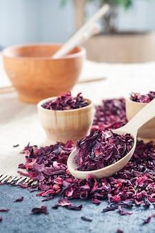 Chá de hibisco seco em colher de pau e xícaras pequenas sobre mesa com tapete de palha