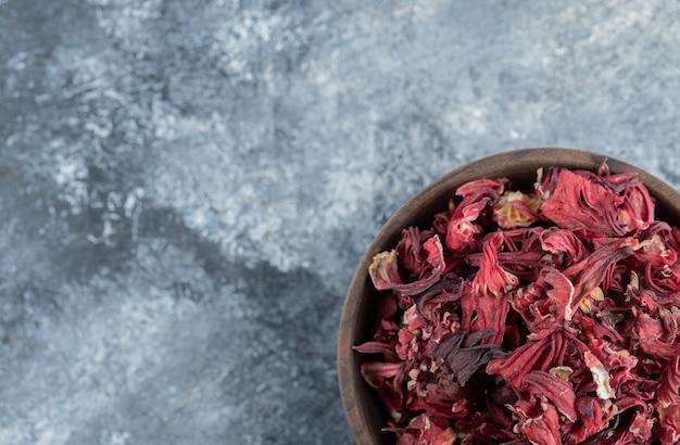Chá de hibisco seco em uma tigela de madeira.