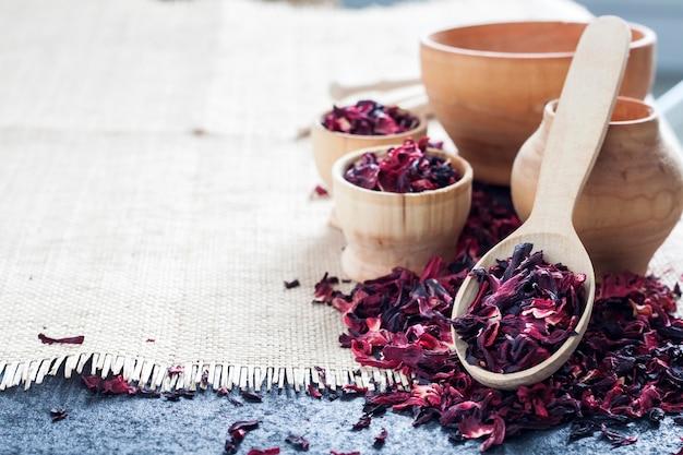 Chá de hibisco seco na colher de pau e xícaras pequenas sobre uma mesa com tapete de palha. copie o espaço