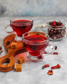 Chá de hibisco vermelho quente em uma caneca de vidro em concreto com pétalas de hibisco seco